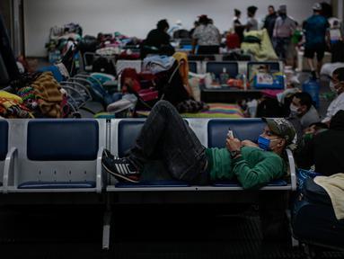 """Imigran Kolombia yang terdampar tinggal di Bandara Internasional Guarulhos, di Guarulhos, dekat Sao Paulo, Selasa (26/5/2020). Lebih dari 200 warga Kolombia terlantar di bandara terbesar di Brasil ini menunggu """"penerbangan kemanusiaan"""" dari pemerintah mereka. (Miguel SCHINCARIOL/AFP)"""