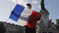 """Seorang demonstran memegang bendera Prancis dengan slogan """"Freedom of Speech"""" selama demonstrasi di Paris (18/10/2020). Pembunuh Samuel merupakan pria kelahiran Moskow berusia 18 tahun yang ditembak mati oleh polisi. (AP Photo/Michel Euler)"""