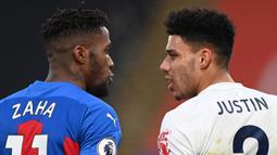 Striker Crystal Palace, Wilfried Zaha (kiri) bersitegang usai ditekel bek Leicester City, James Justin (kanan) dalam laga lanjutan Liga Inggris 2020/21 pekan ke-16 di Selhurst Park, Senin (28/12/2020). Crystal Palace bermain imbang 1-1 dengan Leicester City. (AFP/Facundo Arrizabalaga/Pool)