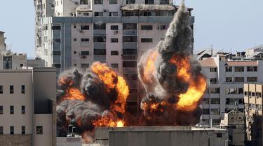 Bola api meletus dari gedung yang menampung berbagai media internasional, termasuk The Associated Press, setelah serangan udara Israel di Kota Gaza, Sabtu (15/5/2021). Serangan terjadi satu jam usai militer Israel memerintahkan orang-orang untuk mengungsi dari gedung. (Mahmud Hams/Pool Photo via AP)