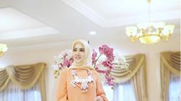 Gaun warna oranye yang sederhana menjadi terlihat fashionable saat dikenakan Syahrini. Tak lupa juga dihiasi dengan kalung cantik. (Liputan6.com/Instagram/@princessyahrini)