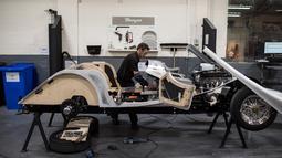 Pekerja menyelesaikan pembuatan mobil klasik dengan bahan dasar kayu ash di pabrik mobil Morgan Motor Company di Malvern, Birmingham, Inggris (13/8/2019). Produksi mobil klasik ini masih menggunakan cara manual tanpa dibantu robot. (AFP Photo/Oli Scarff)