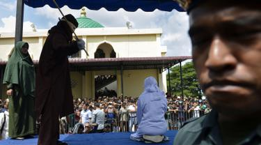 Seorang wanita berusia 19 tahun menjalani hukuman cambuk di depan umum di Banda Aceh (31/1). Dua remaja AS laki-laki (19) dan NS perempuan (19) dicambuk setelah mereka ketahuan berpelukan di depan umum. (AFP Photo/Chaideer Mahyudin)