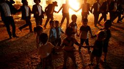 Anak-anak menari di samping api unggun selama perayaan hari libur Yahudi Lag Ba-Omer di Shearim, Yerusalem, (25/5). Lag Ba-Omer merupakan hari libur Yahudi yang dirayakan pada hari ke-33 dari Penghitungan Omer. (REUTERS/Ronen Zvulun)