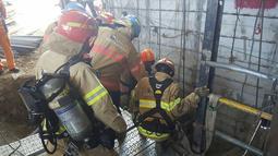 Petugas penyelamat saat akan turun ke lokasi robohnya konstruksi kereta bawah tanah di Namyangju, dekat Seoul, Korsel, Rabu (1/6). Dugaan sementara, insiden ini dipicu oleh ledakan tabung silinder oksigen di lokasi proyek. (NAMYANGJU FIRE STATION/AFP)