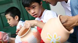 Penyandang disabilitas tampak serius menyelesaikan lukisan keramiknya di Museum Seni Rupa dan Keramik, Jakarta, Jumat (23/10). Kegiatan untuk meningkatkan kemampuan dan keterampilan seni bagi penyandang disabilitas . (Liputan6.com/Immanuel Antonius)