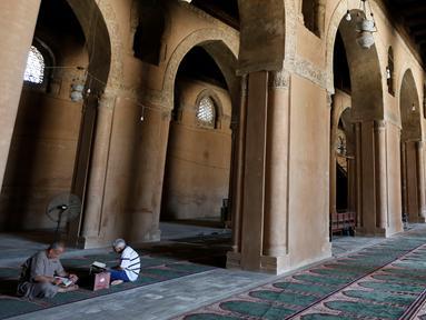 Dua orang pria memanfaatkan bulan suci Ramadan dengan membaca Al Quran di Masjid Ibnu Tulun, Kairo, 2 Juni 2017. Masjid yang dibangun pada 876-879 di masa pemerintahan Ahmad Ibn Tulun ini merupakan masjid tertua kedua di Mesir (REUTERS/Amr Abdallah Dalsh)