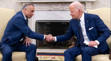 Presiden AS Joe Biden berjabat tangan dengan Perdana Menteri Irak Mustafa Al-Kadhimi (kiri) di Kantor Oval Gedung Putih.  (AFP/SAUL LOEB)