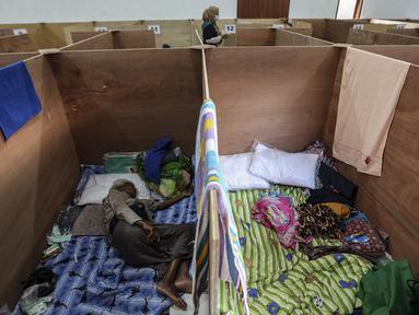 Pengungsi Gunung Merapi tidur dalam bilik lokasi pengungsian di Desa Glagaharjo, Sleman, Jawa Tengah, Rabu (18/11/2020). Kondisi Gunung Merapi yang memasuki level siaga membuat beberapa desa dengan radius 5 Km dari puncak Gunung Merapi mengungsikan penduduknya. (Liputan6.com/Johan Tallo)