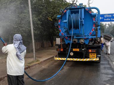 Petugas menyemprotkan air ke pohon-pohon di pinggir jalan New Delhi, India, Rabu (6/11/2019). Hal tersebut dilakukan dalam upaya untuk mengurangi polusi udara dengan memerangi akumulasi debu. (Photo by Prakash SINGH / AFP)