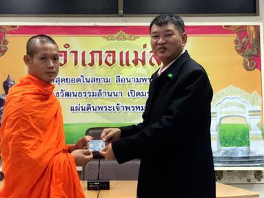 Pelatih sepakbola, Ekapol Chantawong menerima kartu identitas sebagai warga negara Thailand di distrik Mae Sai, Rabu (8/8). Korban gua Thailand tersebut selama ini hidup tanpa memiliki status kewarganegaraan (Chiang Rai Public Relations Office via AP)