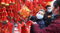Orang-orang mengenakan masker saat berbelanja dekorasi untuk perayaan Imlek Tahun Tikus Logam di sebuah pasar di Provinsi Anhui, China, 24 Januari 2020. Otoritas China dengan cepat membangun rumah  sakit yang didedikasikan untuk merawat pasien yang terjangkit virus corona. (Chinatopix via AP)