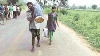 Dana Majhi (kiri), menggendong jenazah istrinya dan berjalan hingga 12 km menuju desa untuk dikremasi. Dana Majhi, didampingi putrinya yang terus menangis sepanjang jalan. Foto : indianexpress.