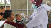 Bidan lengkap dengan baju Alat Pelindung Diri (APD) mengukur suhu tubuh pada anak di Posko Imunisasi, Kelurahan Bakti Jaya, Tangerang Selatan, Senin (11/5/2020). Pelayanan imunisasi tetap berjalan sesuai jadwal meski pandemi Covid-19. (Liputan6.com/Fery Pradolo)