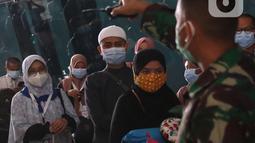Petugas mengatur rombongan jemaah umrah setibanya mereka di Bandara Soekarno Hatta, Tangerang, Selasa (29/12/2020). Rombongan jemaah umrah yang baru tiba di Indonesia tersebut diarahkan untuk melakukan karantina di tempat yang telah disediakan oleh pemerintah. (Liputan6.com/Angga Yuniar)