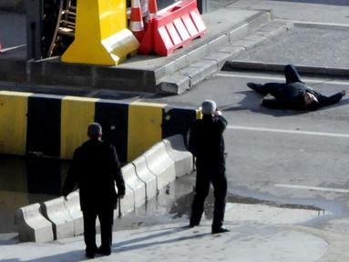 Polisi Turki mengarahkan senjata kepada seorang pria yang tergeletak di tanah, di luar kantor polisi di Gaziantep, Selasa (10/1). Pria itu ditembak mati, setelah sebelumnya mencoba memaksa masuk ke dalam kantor polisi dan menembak petugas. (AFP PHOTO/STR)