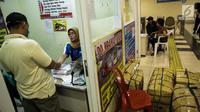Suasana pembelian tiket bus antar provinsi di Terminal Pulo Gebang, Jakarta, Kamis (8/6). Penjual mengeluhkan sepinya pembelian tiket bus di Pulo Gebang karena masih banyaknya terminal bayangan yang beroperasi. (Liputan6.com/Faizal Fanani)