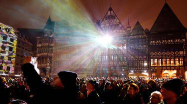 """Ratusan warga menyaksikan gedung-gedung disinari cahaya saat pembukaan resmi festival cahaya """"Luminale"""" di Frankfurt, Jerman, (18/3). (AP Photo / Michael Probst)"""