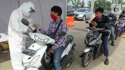 Pengendara motor mengikuti rapid test Covid-19 gratis di danau Asya Jakarta Garden City, Jakarta Timur, Kamis (28/5/2020). Perumahan Asya memberikan layanan rapid test sebagai upaya membantu pemerintah dalam menekan penyebaran Covid-19 dengan konsep drive thru. (Liputan6.com/Fery Pradolo)