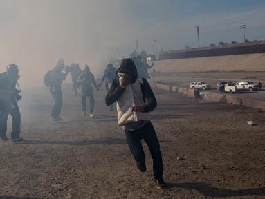 Imigran menghindari gas air mata petugas patroli perbatasan AS di dekat pagar pembatas antara Meksiko dan Amerika Serikat di Tijuana, Meksiko (25/11). Walikota Tijuana telah menyatakan krisis kemanusiaan di kota perbatasannya. (AP Photo/Rodrigo Abd)