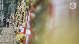 Pejalan kaki melintas dekat karangan bunga yang dipajang di depan Markas Kodam Jaya, Jakarta, Senin (23/11/2020). Ratusan karangan bunga dikirim masyarakat sebagai bentuk dukungan terhadap TNI dan Polri atas tindakan tegas kepada pelanggar protokol kesehtan Covid-19. (merdeka.com/Iqbal S Nugroho)