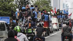 Mahasiswa menaiki sejumlah truk saat konvoi menuju Gedung DPR/MPR, Jakarta, Kamis (8/10/2020). Mahasiswa ini rencananya akan menggelar aksi menolak UU Cipta Kerja. (Liputan6.com/Johan Tallo)