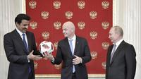 Presiden FIFA Gianni Infantino (tengah) memberikan bola kepada Emir Qatar Sheikh Tamim bin Hamad al-Thani disaksikan Presiden Rusia Vladimir Putin. Qatar bakal jadi tuan rumah Piala Dunia 2022. (Alexei Nikolsky, Sputnik, Kremlin Pool Photo via AP)