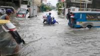 Warga berkendara ke tempat kerja meski banjir melanda Metropolitan Manila, Filipina, Jumat (20/7). Selain bagian Metropolitan Manila, banjir juga terjadi di provinsi lain. (AP Photo/Bullit Marquez)