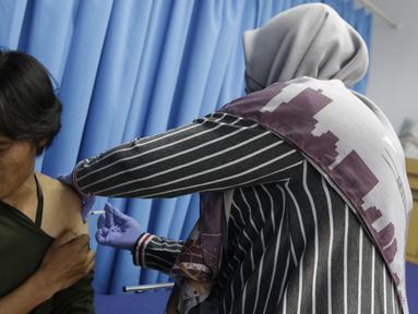 Seorang wartawan saat disuntik vaksin polio jelang SEA Games 2019 di Kantor Kemenpora, Jakarta, Rabu (13/11). Suntik vaksin tersebut untuk mengantisipasi wabah polio di Filipina. (Bola.com/M Iqbal Ichsan)