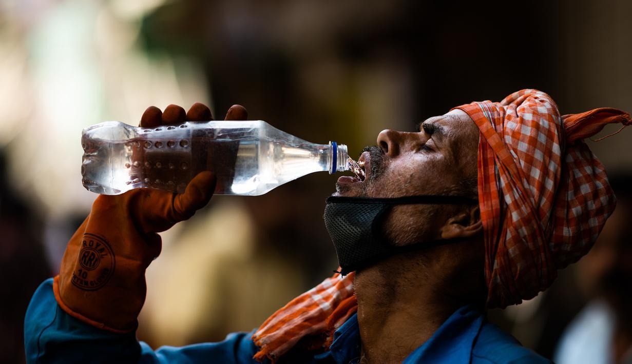 Pekerja meminum air dari botol di tengah meningkatnya suhu di New Delhi, India, Rabu (27/5/2020). India dilanda gelombang panas dan krisis air bersih di tengah upaya menangani pandemi virus corona COVID-19. (Jewel SAMAD/AFP)