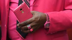 Fashionista Kenya, James Mwangi Maina memegang ponselnya sambil memamerkan setelan jasnya yang senada dengan pakaian dan aksesorisnya, termasuk masker di jalanan Nairobi, 5 Agustus 2020. Mwangi mengklaim dirinya memiliki penampilan terbaik dan paling stylish di Afrika. (Simon MAINA/AFP)