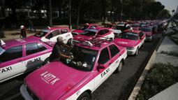 Sopir taksi memblokir bundaran monumen Angel of Independence di Jalan Paseo de la Reforma, Mexico City, Meksiko, Senin (12/10/2020). Para sopir taksi menuntut kondisi yang sama dengan layanan transportasi online, seperti peraturan dan biaya pemerintah. (AP Photo/Fernando Llano)