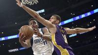 Guard Dallas Mavericks Yogi Ferrell coba menghindari blok center Los Angeles Lakers Brook Lopez pada laga NBA di Staples Center, Rabu (28/3/2018) atau Kamis (29/3/2018) WIB. (AP Photo/Reed Saxon)