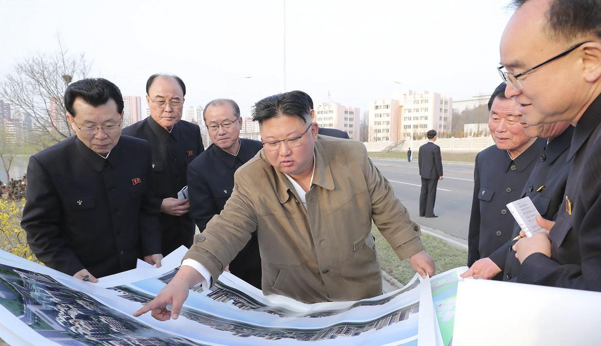 Pemimpin Korea Utara Kim Jong-un memberikan arahan kepada stafnya saat mengunjungi lokasi konstruksi pembangunan gedung apartemen di tepi Sungai Pothong, Korea Utara, Kamis (1//4/2021)..( STR/KCNA VIA KNS/AFP)