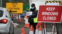 Lalu lintas warga saat hendak melakukan tes virus corona di pusat pengujian drive-in di Bandara Glasgow, saat Inggris terus melakukan lockdown. (Andrew Milligan / POOL / AFP)