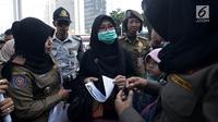Petugas Satpol PP meminta pengunjung mengganti pakaian bertagline '#2019GantiPresiden' yang dikenakannya selama car free day (CFD), Jakarta, Minggu (6/5). CFD tidak boleh dimanfaatkan untuk kepentingan partai politik dan SARA. (Merdeka.com/Iqbal Nugroho)