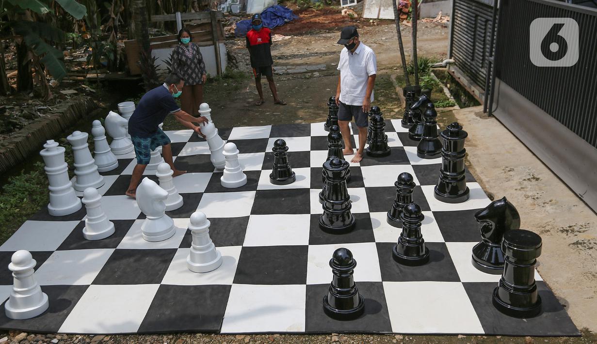 Warga bermain catur raksasa sambil menunggu waktu berbuka puasa di Pondok Betung, Tangerang Selatan, Kamis (14/5/2020). Kegiatan olahraga menjelang berbuka puasa sambil mengasah otak dilakukan agar tidak jenuh selama PSBB diterapkan di tengah pandemi Covid-19. (Liputan6.com/Fery Pradolo)