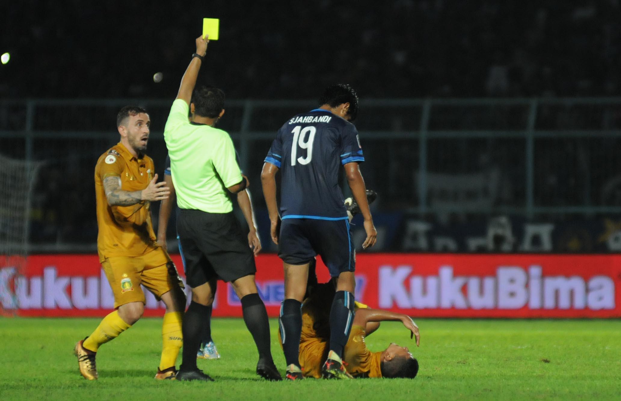 Gelandang Arema FC, Hanif Sjahbandi, melakukan tekel horor ke pemain Bhayangkara FC, T.M Ichsan, dalam pertandingan terakhir Grup E Piala Presiden 2018 di Stadion Kanjuruhan, Malang, Senin (30/1/2018). (Bola.com/Iwan Setiawan)
