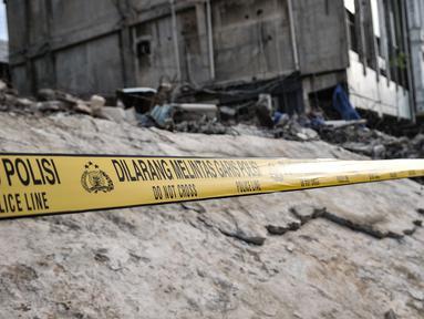 Garis polisi terpasang di sekitar lokasi bangunan roboh di Jalan Kyai Caringing, Gambir, Jakarta, Kamis (3/9/2020). Bangunan empat lantai itu roboh dan menimpa kabel listrik serta reruntuhannya menutupi jalan sehingga arus kendaraan arah Harmoni-Grogol sempat dialihkan. (merdeka.com/Iqbal Nugroho)