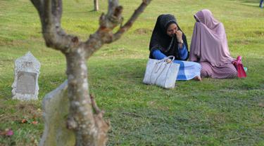 Dua perempuan Aceh berdoa di pemakaman massal Ulhee Lheue, Banda Aceh, Sabtu (26/12/2015).  Doa tersebut untuk keluarga mereka yang terkena bencana Tsunami pada 26 Desember 2014. (AFP Photo/ Chaideer Mahyuddin)