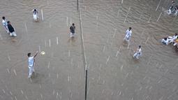Meski sekolah mereka terkena banjir, siswa Budi Utomo tetap bermain voli, Jakarta, Senin (9/2/2015). (Antara Foto/Fanny Octavianus)