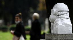 """Wanita yang memakai masker wajah berjalan di dekat patung marmer yang didedikasikan untuk dokter, perawat, dan petugas kesehatan tanpa judul """"Tentara anti Covid-19"""", di Taman Pincio di Roma tengah (4/11/2020). (AFP/Filippo Monteforte)"""