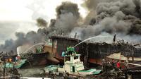 Para pekerja mencoba membantu memadamkan api di kapal nelayan di Pelabuhan Benoa, Denpasar, Bali, Senin (9/7). Kebakaran semakin membesar karena angin cukup kencang. (SONNY TUMBELAKA/AFP)