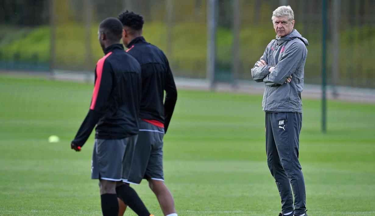 Pelatih Arsenal, Arsene Wenger (kanan) melihat para pemainnya berlatih di tempat latihan London Colney Arsenal, Inggris (25/4). Arsenal akan menghadapi wakil Spanyol, Atletico Madrid pada leg pertama babak semifinal Liga Europa. (AFP Photo/Ben Stansall)
