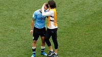 Striker Uruguay, Edinson Cavani menghibur rekan setimnya, setelah kalah atas Prancis pada akhir laga perempat final Piala Dunia 2018 di Nizhny Novgorod Stadium, Jumat (6/7). Timnas Uruguay tersingkir usai ditumbangkan Prancis 0-2 . (AP/Hassan Ammar)