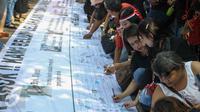 Para pendukung Ahok membubuhkan tandatangan saat aksi di depan Balaikota, Jakarta, Sabtu (13/5). Massa pendukung Ahok menggelar aksi pengumpulan KTP untuk membebaskan Ahok dari jeratan vonis dua tahun penjara. (Liputan6.com/Yoppy Renato)