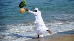 """Umat Hindu melempar sesajen selama upacara doa Melasti, festival penyucian yang diadakan beberapa hari sebelum """"Nyepi"""" di Pantai Kuta, Bali (11/3/2021). Hari Raya Nyepi tahun ini jatuh pada tanggal 14 Maret 2021. (AFP/Sonny Tumbelaka)"""