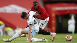 Pemain Manchester United Paul Pogba (kanan) berebut bola dengan pemain West Ham United Declan Rice pada pertandingan Liga Inggris di Old Trafford, Manchester, Inggris, Rabu (22/7/2020). Pertandingan berakhir dengan skor 1-1. (Clive Brunskill/Pool via AP)
