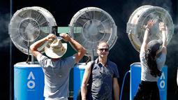 Sejumlah penonton mendinginkan tubuhnya dengan kipas pendingin selama pertandingan Australia Terbuka 2018 di Melbourne, Australia, (16/1). Teriknya matahari membuat peserta dan penonton kepanasan. (AP Photo / Ng Han Guan)