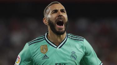 Penyerang Real Madrid, Karim Benzema berselebrasi usai mencetak gol ke gawang Sevilla pada pertandingan lanjutan La Liga Spanyol di stadion Ramon Sanchez Pizjuan (22/9/2019). Gol Benzema di menit ke 64 menjadi satu-satunya gol yang tercipta di pertandingan ini. (AP Photo/Miguel Morenatti)
